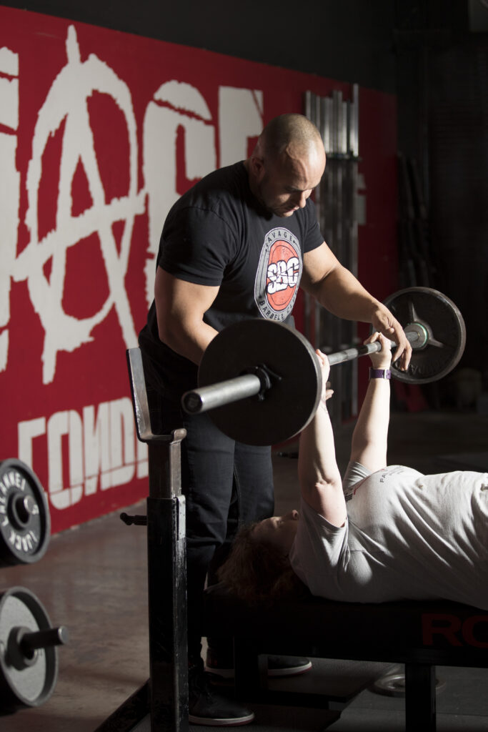Jeron Kerrige, owner of Savage Barbell Club in Tigard, helps a client with the bench press. Photo by Jaime Valdez